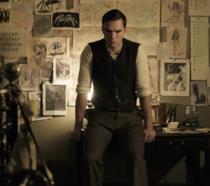 Nicholas Hoult nei panni di Tolkien seduto su una scrivania, sullo sfondo di una parete con disegni