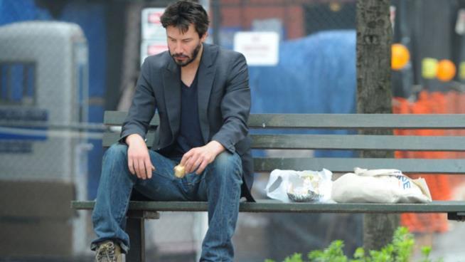 L'attore Keanu Reeves mangia un panino seduto con aria abbattuta su una panchina