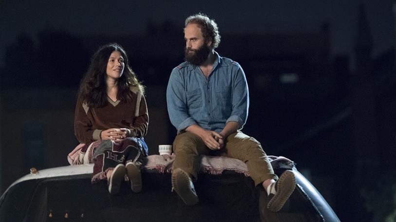 Katja Blichfeld e Ben Sinclair seduti sul tettuccio di un'auto, su sfondo buio