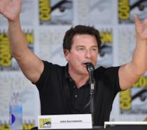 Mezzobusto di John Barrowman con le braccia alzate su sfondo pubblicitario del SDCC