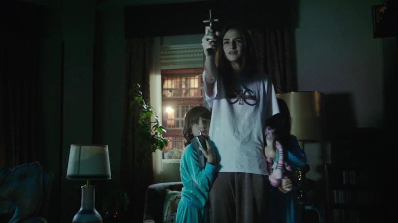 Veronica tende un crocifisso verso un demone per tentare di proteggere sé e i propri fratellini