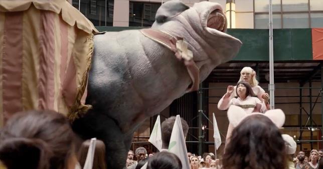 Okja esce da un tendone urlando e spaventando il pubblico, la presentatrice e la piccola Mija