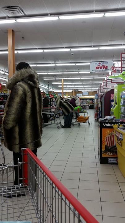 Due uomini in fila alle casse del supermercato con la stessa pelliccia