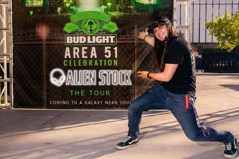 Matty Roberts con dietro il cartellone ufficiale del festival Alienstock