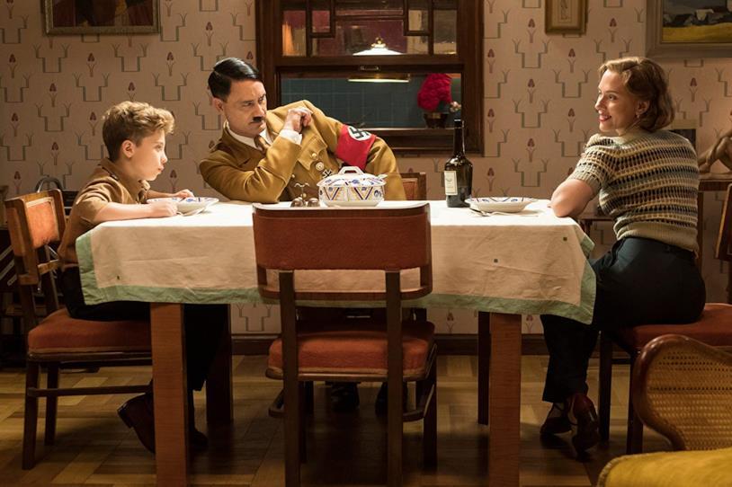 Roman Griffin Davis, Taika Waititi e Scarlett Johansson seduti al tavolo in una scena del film