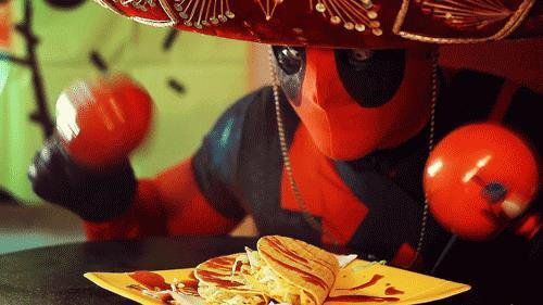 Gif di Deadpool che festeggia davanti a un piatto di