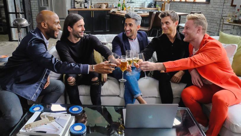Il cast di Queer Eye seduto su un divano, mentre brinda