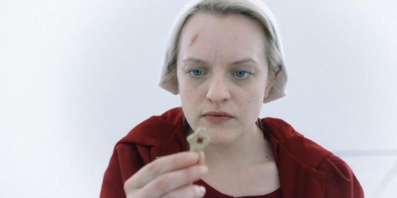 Un mezzo primo piano di Elisabeth Moss osserva una piccola chiave in The Handmaid's Tale