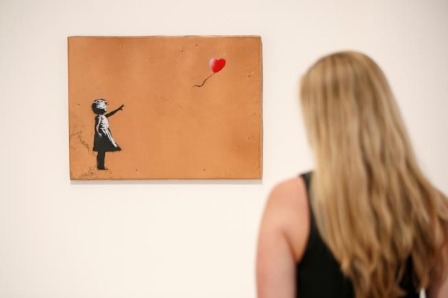 Una foto in cui è ritratto il dipinto Balloon Girl di Banksy