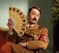 Taika Waititi seduto e vestito da Adolf Hitler in una scena di Jojo Rabbit