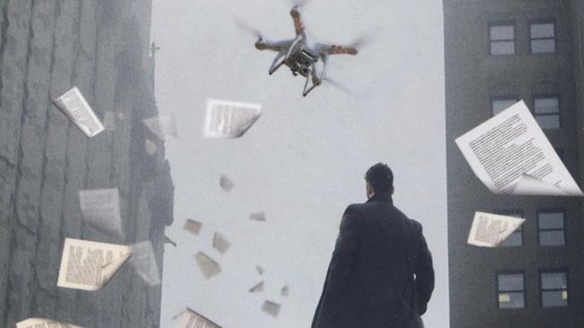 Un uomo in mezzo a fogli volanti mentre guarda un drone