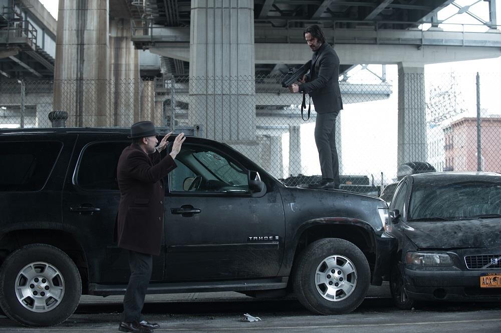 John Wick punta un'arma contro un uomo