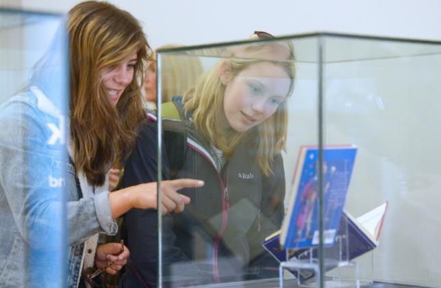 Due donne osservano una teca che contiene alcune edizioni di Harry Potter