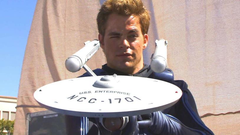 Chris Pine con un'espressione sorniona osserva il retro di un modellino dell'astronave U.S.S. Enterprise del Capitano Kirk