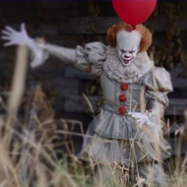 Il nuovo Pennywise nel remake di IT, mentre tiene un palloncino rosso