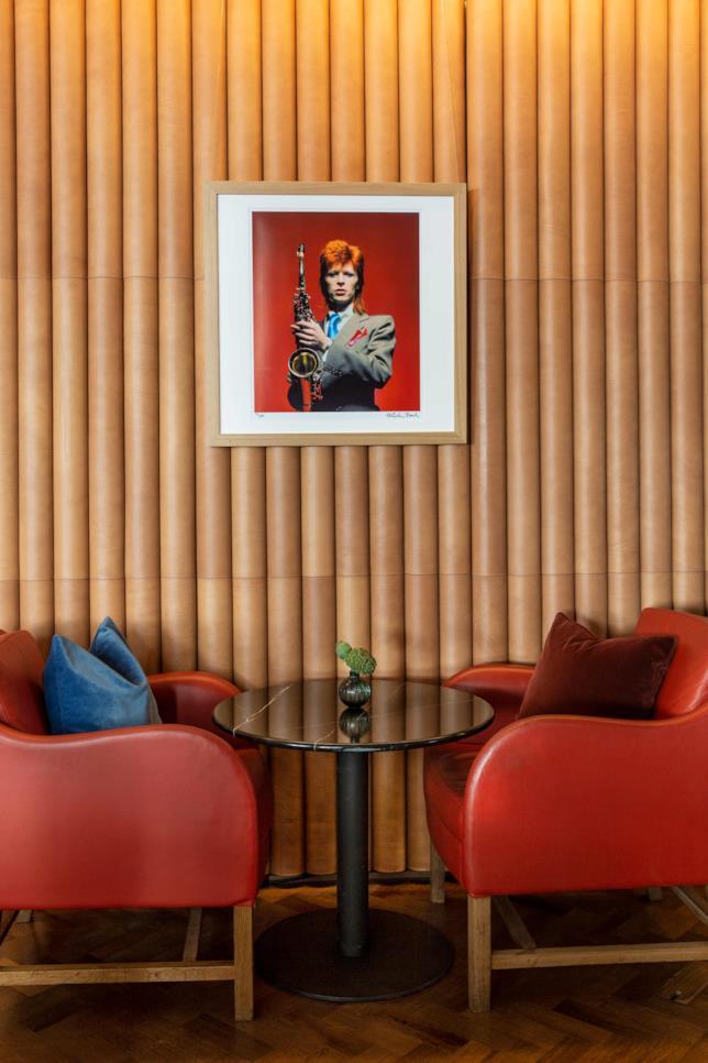 Due poltrone, un tavolino e una foto di David Bowie appesa alla parete del bar Ziggy's di Londra