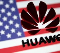 Il logo di Huawei in primo piano; sullo sfondo la bandiera degli USA