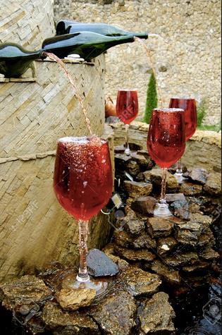 Una fontana eroga vino rosso sulle rocce