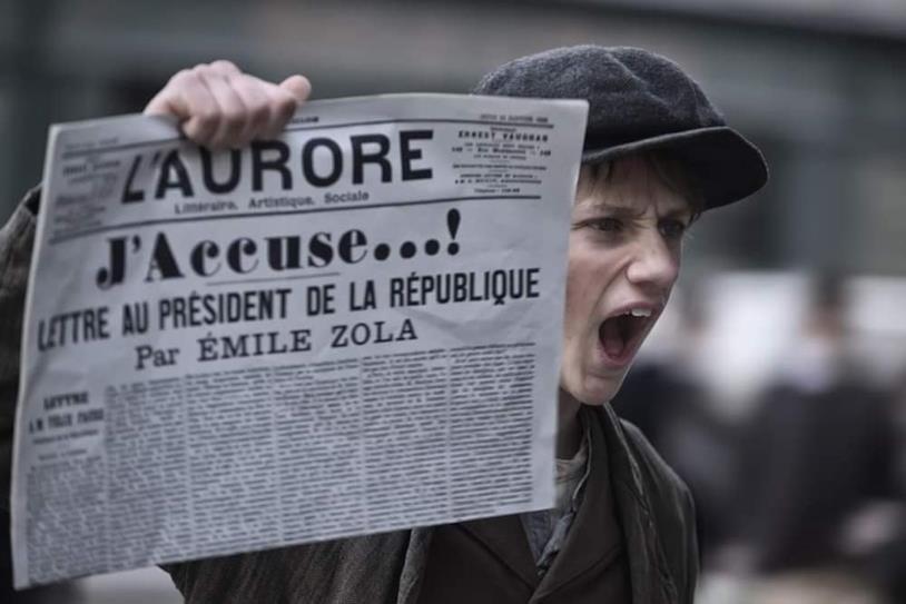 Uno strillone mostra la prima pagina de L'Aurore in una scena di J'Accuse
