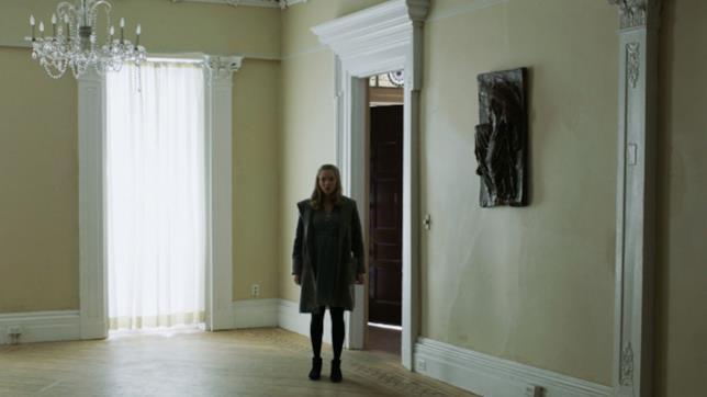 Amanda Seyfried in piedi in una stanza vuota in una scena di First Reformed