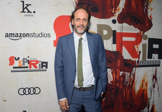Il regista Luca Guadagnino posa davanti al poster di Suspiria