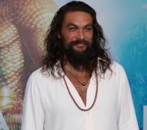 Mezzobusto di Jason Momoa in camicia, con cartellone promozionale di Aquaman alle spalle