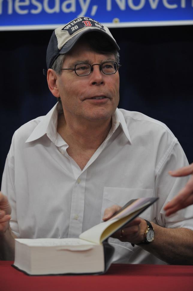 Stephen King in primo piano con un libro