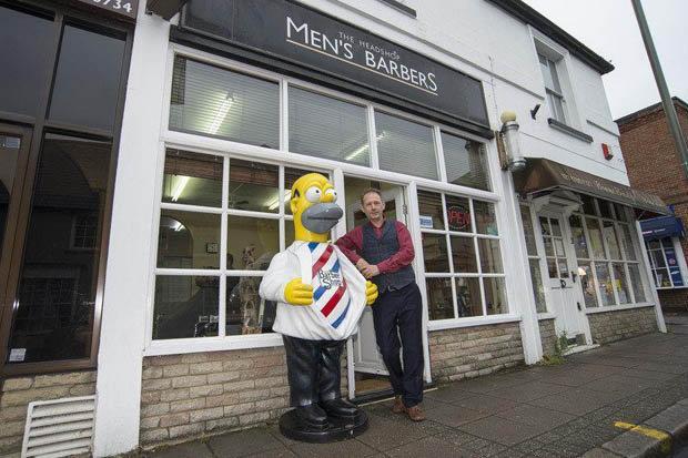 La statua di Homer Simpson davanti al negozio di un barbiere