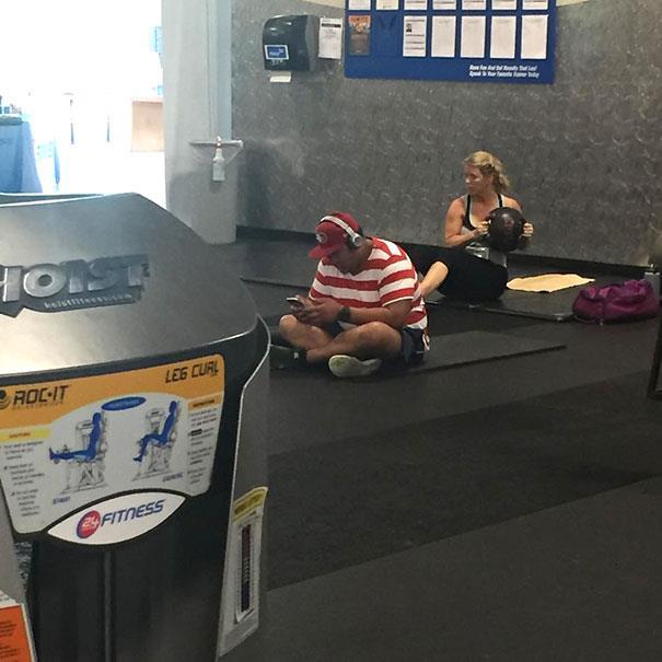 In palestra: uomo seduto a terra con cuffie e smartphone