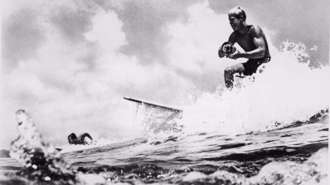 Bruce Brown surfa con la macchina da presa nella mano in una foto d'archivio