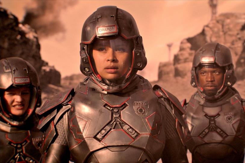Mezzibusti di Frankie Adams nei panni di Bobbie Draper e compagni di squadra in tuta spaziale, sullo sfondo di Marte
