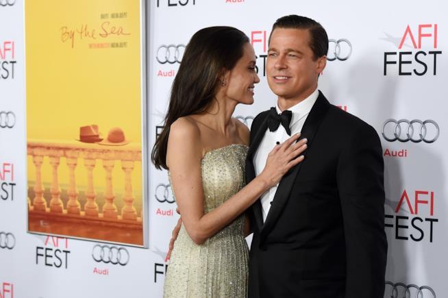 Primo piano di Angelina Jolie e Brad Pitt in atteggiamenti affettuosi