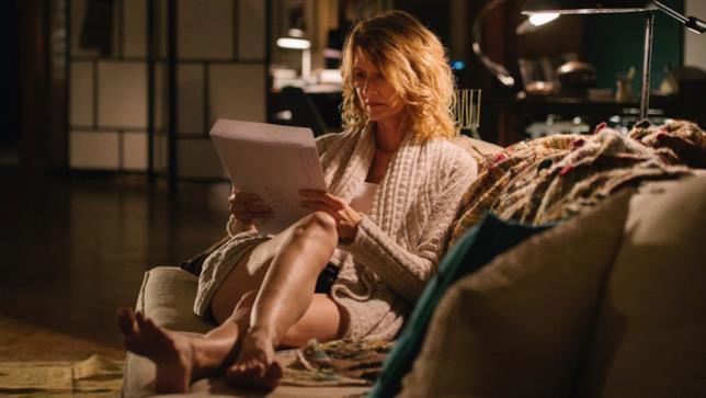 Laura Dern in accappatoio su un divano, con una grande busta in mano