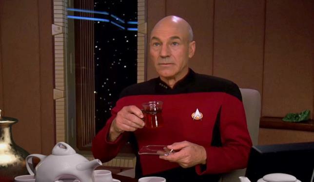 Mezzobusto di Patrick Stewart con l'uniforme di Picard, seduto alla scrivania del suo ufficio sull'Enterprise