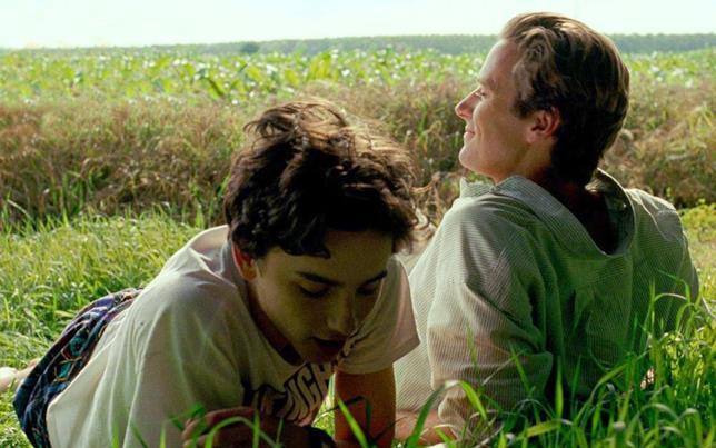 Timothée Chalamet ed Armie Hammer stesi sull'erba in una scena del film