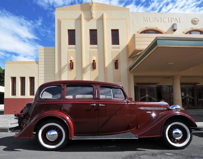 Una sala cinematografica con un'auto d'epoca parcheggiata davanti