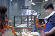 Due volontari che testano il braccio robotico Arm-A-Dine