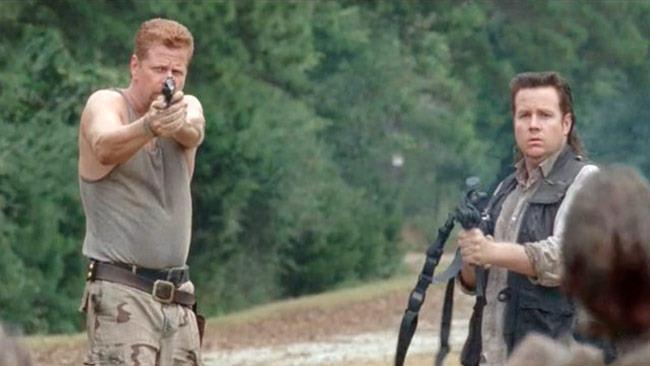 Michael Cudlitz e Josh McDermitt armati e minacciosi, con foresta sullo sfondo
