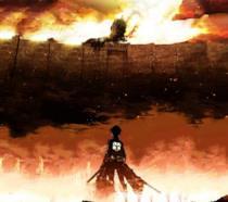Il protagonista Eren contro il Gigante Colossale dietro le mura della città