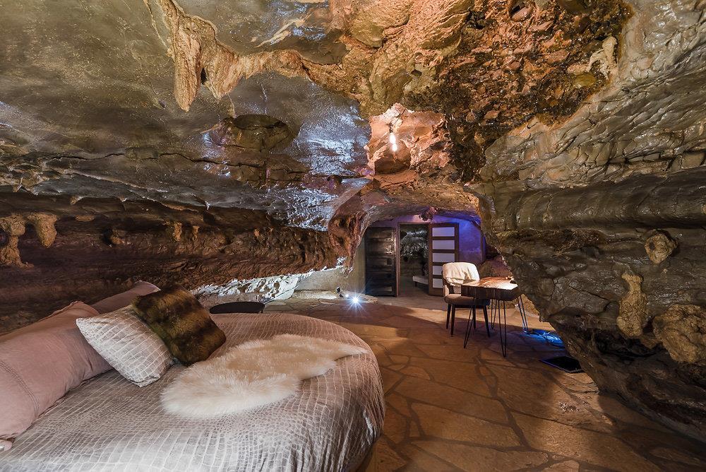 L'interno della Beckam Creek Cace Lodge: camera da letto con angolo studio e parete rocciosa