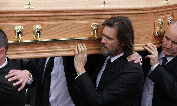 Primo piano di Jim Carrey mentre sorregge la bara di Cathriona White