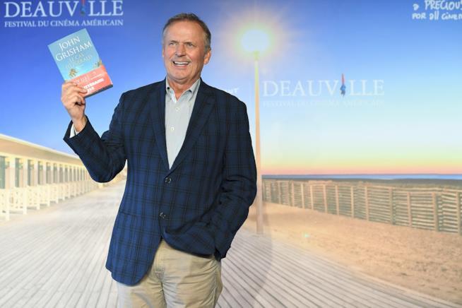 John Grisham con il suo romanzo in mano