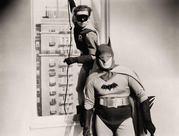 Batman in piedi in un appartamento, mentre Robin entra dalla finestra