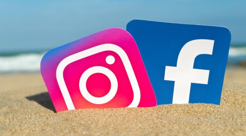 Primo piano dei loghi di Instagram e Facebook tra la sabbia
