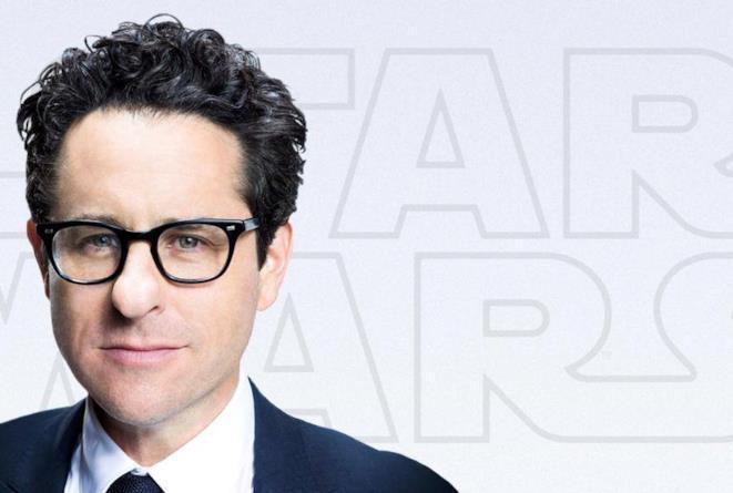 J.J. Abrams con sullo sfondo il logo di Star Wars
