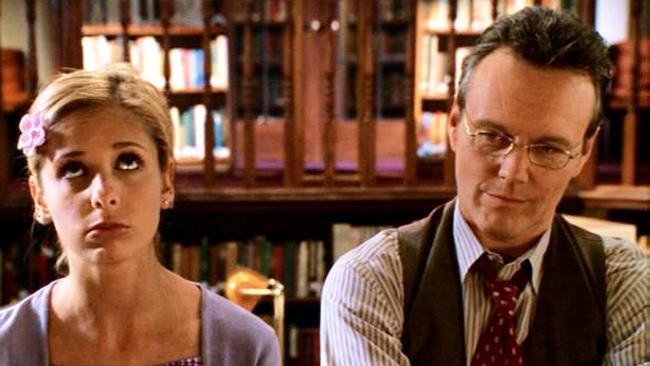 Giles e Buffy con aria pensierosa in biblioteca