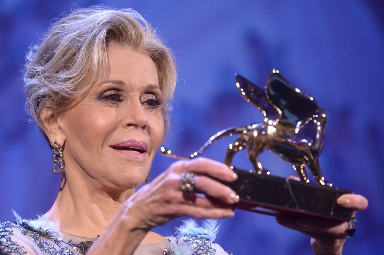 Jane Fonda osserva il Leone d'Oro alla carriera appena ricevuto a Venezia 74.
