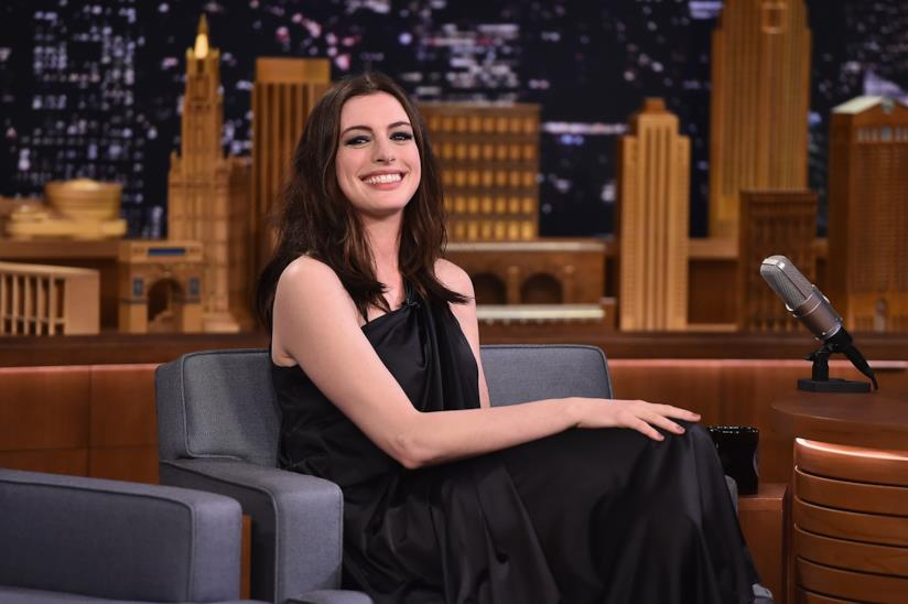 Anne Hathaway seduta con un grande sorriso