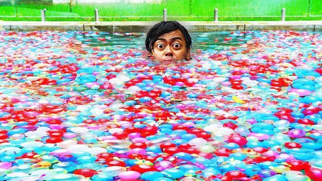 Lo YouTuber Guava Juice in una piscina ricoperta di palloncini d'acqua