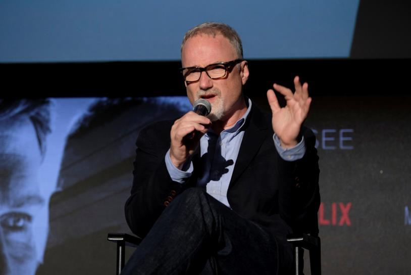 Il regista David Fincher seduto in poltrona, impegnato a parlare con un microfono in mano
